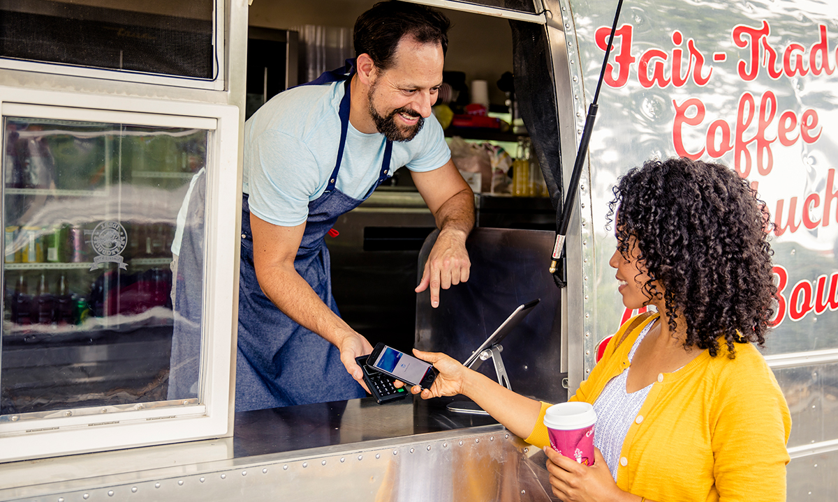 Woman making a payment at a foodtruck